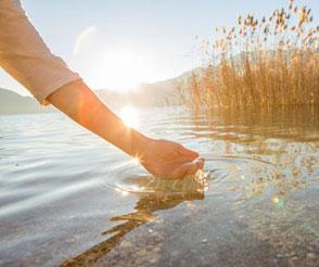 Der Tag der Stille beim MBSR-Kurs in Frankfurt, symbolisiert durch eine Hand, die durch das Wasser schöpft und Ruhe ausstrahlt.