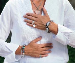 Eine Frau mit weißem Shirt und Schmuck am Handgelenk und Fingern hält sich eine Hand auf die Brust, eine auf den Bauch. Das Foto symbolisiert den achtsamen Umgang mit sich selbst, der im MBSR-Kurs Frankurt mit Heike Merkle erlernt wird.