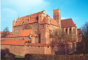 Marienburg Общий комплекс оборонительных укреплений справа с высокими готическими окнами выступаеи замковая капелла