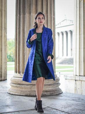 Ein eleganter knielanger Gehrock aus bestickter blauer Seide. Er changiert leicht grün und ist mit tannengrüner Seide abgesetzt.