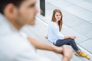 junges-paar-sitzt-versetzt-auf-treppe-sie-schaut-ihn-an-liebe-partnerschaft-moderne-paarfotos-paerchen-zu-zweit-duesseldorf-duisburg