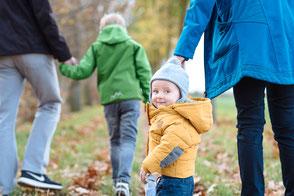 kinder-und-eltern-laufen-gemeinsam-familienshooting-natuerliche-familienfotos-herbstliches-familienshooting-familienfotograf-duisburg-duesseldorf