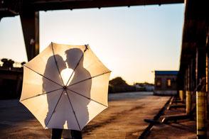 junges-paar-steht-im-gegenlicht-hinter-einerm-regenschirm-paerchenfotos-fotos-zu-zweit-paarfotos-duesseldorf-duisburg-industrie