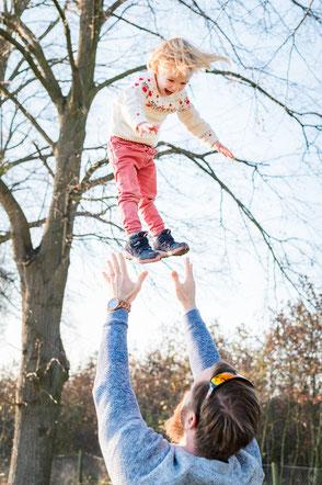 vater-wirft-kind-hoch-lustige-familienfotos-fotoshooting-familienfotograf-familienshooting-duisburg-duesseldorf