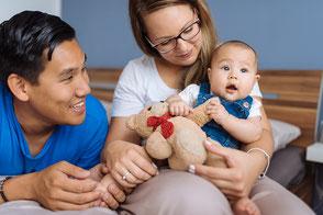 eltern-mit-baby-zu-hause-familienfotos-im-schlafzimmer-babyfoto-duesseldorf-homestory-zuhause-duisburg-mama-und-papa