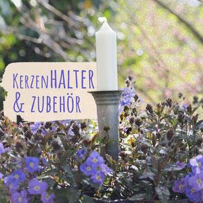 """Rosafarbener Kerze in einem extravaganten silberfarbenen Kerzenhalter auf einer Kaffeekanne aus Emaille. Im Hintergrund vereiste Bäume und die Aufschrift """"Kerzenhalter & Zubehör""""."""