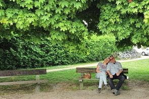 Ina und Stephan auf der Parkbank unter Bäumen
