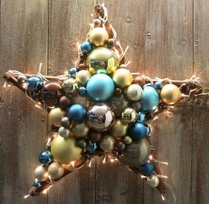 Handgefertigter Stern aus Glaskugeln in braun, gold und blau mit Beleuchtung.
