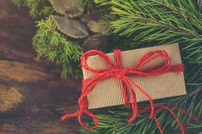 Geschenk mit roter Schleife am Tannenzweig