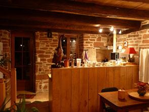 Grès rouge et bois donnent une ambiance chaude au séjour et à la cuisine.