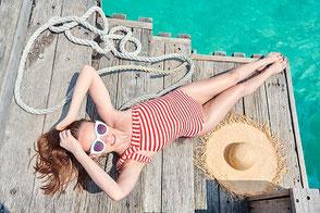 Endlich Urlaub: Eine Familie mit zwei Kindern fährt mit einem roten Auto ans Meer in den Urlaub an die Küste. Sie lachen und freuen sich und sind gut versichert mit dem richtigen Reiseschutz - der Storno-Versicherung gegen Rücktrittskosten auch bei Corona