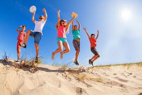 Fröhliche Kinder im Sonnenlicht im Wald auf einer Schulreise oder Schulfahrt, gut versichert mit der Schüler-Reiseversicherung der ERGO