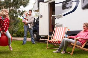 Wohnmobil im Hintergrund, davor eine Familie im Campingurlaub auf dem Campingplatz, gut versichert mit CDW-Versicherung