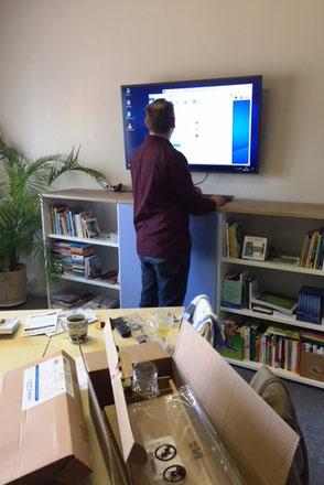Ein Techniker bringt einen Fernseher an der Wand an im Büro von Ina Bärschneider