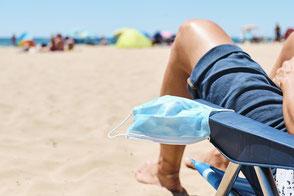 Zwei Freunde mit Maske im Urlaub mit Corona-Reiseschutz versichert haben gut Lachen