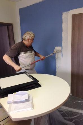 Ein Maler streicht die Wand im ERV-Büro von Ina Bärschneider
