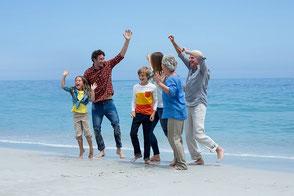 Frau pustet Sand am Meer in den Wind mit einer Reiseversicherung ohne Selbstbeteiligung