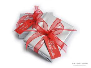 Confezione regalo che riprende i colori del brand e biglietto ad personam scritto a mano