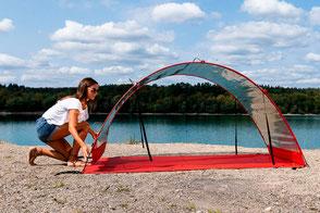 Eine junge Frau, die das HelioTent von HelioVital an einem Seeufer aufbaut.