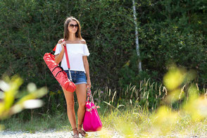 Eine junge Frau, die mit einem HelioTent Sonnenschutz-Zelt und ihrer Tasche in Richtung Strand geht.