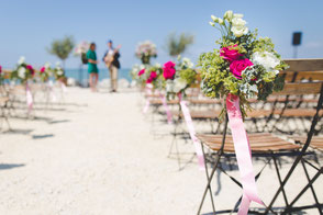 with flowers decorated chairs on beach