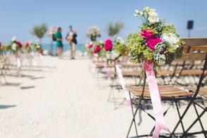 mit Blumen dekorierte Stühle am Strand
