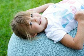 Kindergartenfotografie. Mädchen auf Wal liegend