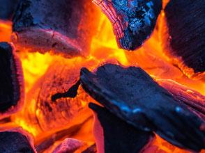 Ausschnitt einer Feuersglut von Holzscheiten. Das Feuer ist das Element der Wandlung und Erneuerung.