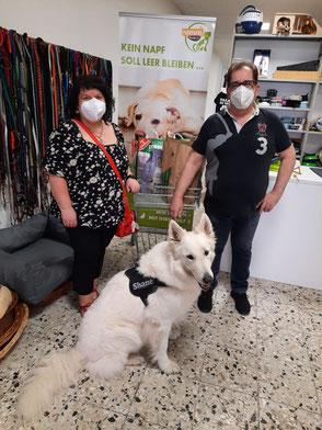 weißer Schäferhund, zwei Menschen mit Spenden