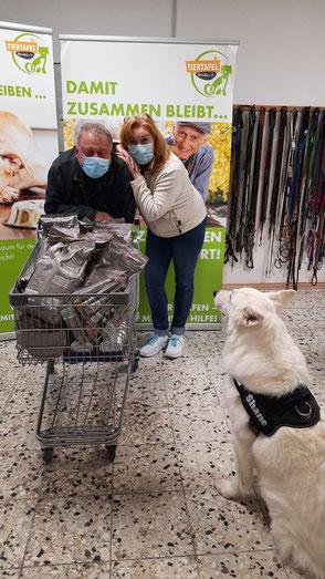 Weißer Schäferhund und Paar mit Futterspenden für die Tiertafe