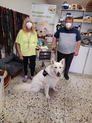 weißer Schäferhund und zwei Personen mit Futterspende