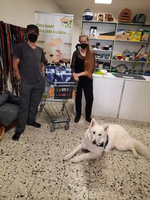weißer Schäferhund liegt vor zwei Peronen mit Futterspenden