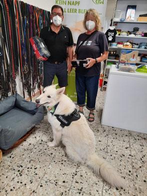 weißer Schäferhund mit zwei Personen und Futterspende