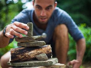 Mann baut einen Turm aus Steinen