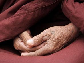 Hände eines Mönchs bei der Meditation