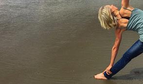 Alexandra Reuter übt das yogische Dreieck am Elbstrand. Yoga ist eine Möglichkeit der Selbstheilung und kann sanft oder herausfordernd, je nach Gesundheitszustand, geübt werden.