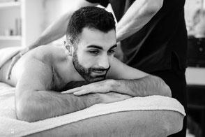 Homme souriant intéressé par un massage