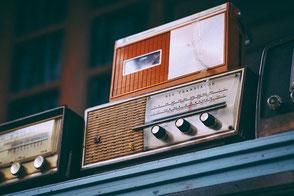 Alte Radios auf Regalbrett.