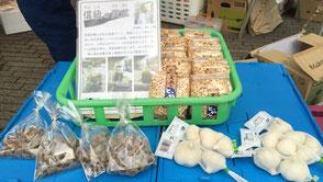 こめる農園∞こめる食堂の大島孝仁さんと、誠子さん。地域の仲間の商品も並ぶ。長野ではポン菓子を「とっかん」という。