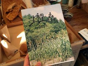 上樫森(かみかしもり)農園、代表の田波憲二さん。上樫森の様子を写真に収めた、自作の本。ページをめくれば、思わず、ほっこり。