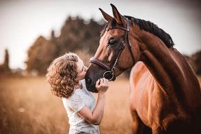 Mädchen mit Locken küsst ihr braunes Pferd auf die Nüstern im Hintergrund ein Sonnenuntergang  fotografiert von der Hunde Fotografin Monkeyjolie