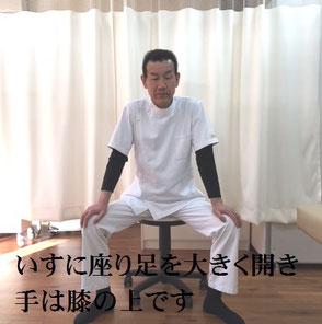 いすに座り足を大きく開き、手はひざの上です。