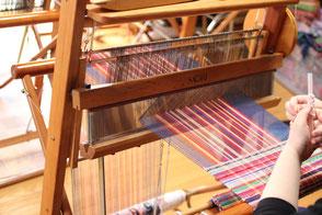 カラフルな糸でさをり織りを織る様子