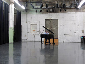 Ein kleiner schwarzer Flügel steht in einer Industriehalle, dahinter sitzt eine Klavierstimmerin, die ihn gerade stimmt.