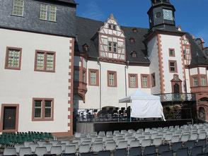 Eine Bühne vor der Mauer eines Renaissanceschlosses, auf der ein weißes Zelt steht. Davor Stuhlreihen.