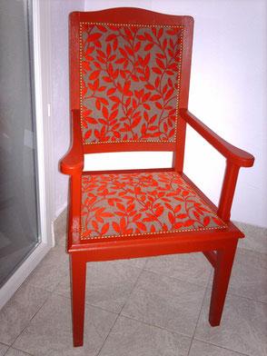 Fauteuil Rustique repeint en rouge et recouvert d'un tissu à motifs de feuilles rouges et taupe finition clous dorés