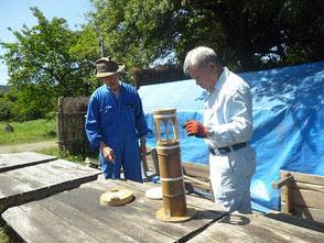 竹灯篭の固定方法を説明する若松さん(左)