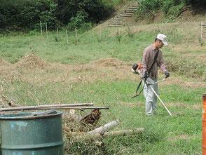 広場の草刈りをする伊藤さん