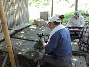 草刈機のチップソーの刃砥ぎをする山田さん