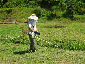 広場の草刈りをする木村会長